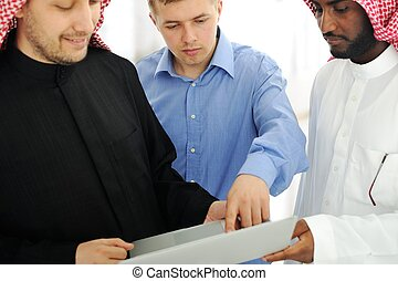 A business team of three planning work in office