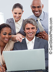 A business team showing ethnic diversity using a laptop