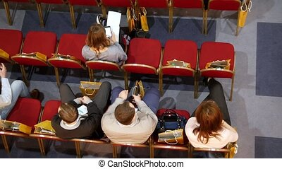 A business training in the hall. People are waiting for the training to start and sitting in their smartphones