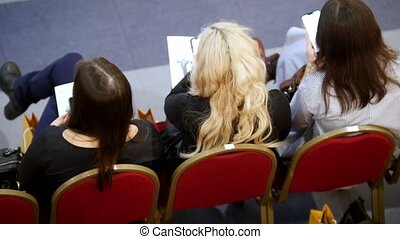 A business training in the hall. Three women are sitting in red armchairs and waiting for the training to start