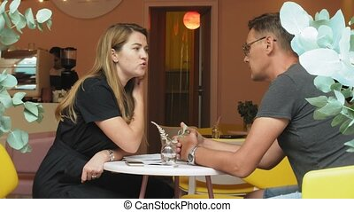 A business woman and a man at their break with their tablet sit in a cafe with yellow walls and discuss a project
