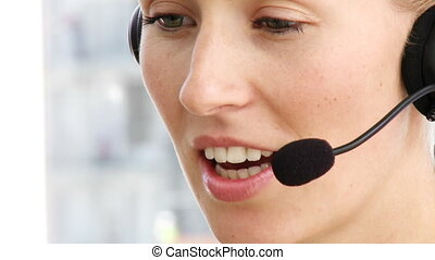 Close-up of business woman talking on headset in a call centre