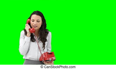 A business woman talking to someone on a red telephone