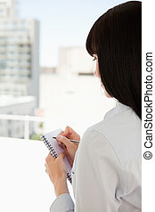 A business woman with her back to the camera begins to write down information that she has though of