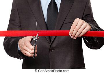 A businessman cutting a satin ribbon - A man cutting a...
