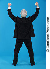 A businessman gesturing a victory sign.