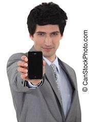 A businessman handing a phone.