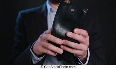 A Businessman Hiding Cash in His Wallet - A businessman...