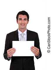 A businessman holding a blank poster.