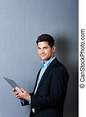 A businessman holding a tablet computer