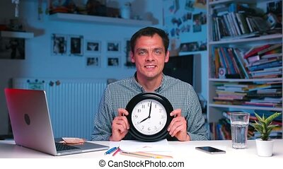 A businessman holds a clock in his hands, the time is 08 00