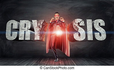 A businessman in a red cape and a mask kicking concrete letters reading 'Crysis' with his foot.
