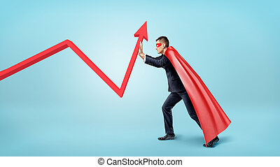 A businessman in a red flowing cape trying to bend a red statistic arrow upwards on blue background.