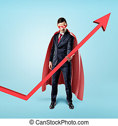 A businessman in a red flowing cape trying to keep the upward looking red arrow with his hand.