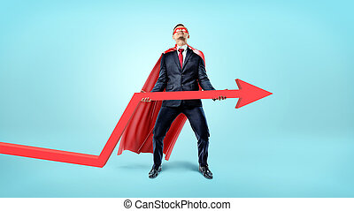 A businessman in a red flowing cape trying to lift a large red arrow upwards on blue background.