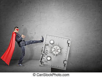 A businessman in a red superhero cape kicking at a giant strongbox to push it over the edge.