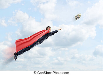A businessman in a superhero cape flying in the sky trying to catch a 100 USD banknote.