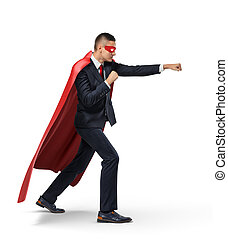 A businessman in a superhero red cape and a mask standing in...