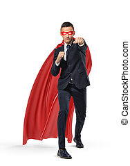 A businessman in a superman red cape and a mask standing in...