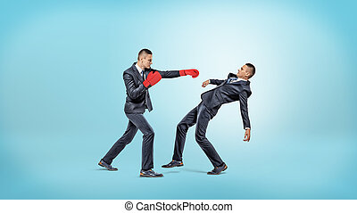 A businessman in boxing gloves fails to punch another man who manages to avoid the kick.