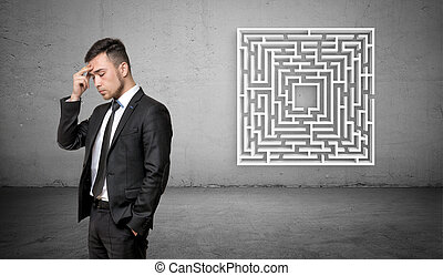 A businessman in deep thought with a white maze on concrete background behind him.