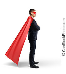 A businessman in superhero cape and mask with hands crossed in side view on white background.