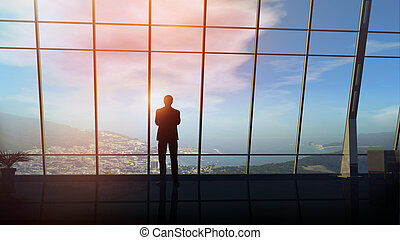 A businessman is standing in front of a window overlooking a coastal town.