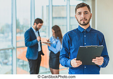 A businessman is standing in the office holding a folder in his hands. During this time, he stands against the background of his colleagues who work on the tablet.
