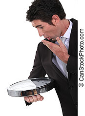 A businessman looking at his abnormal big wristwatch.