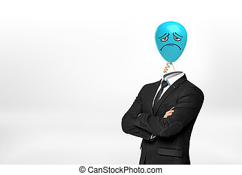 A businessman on white background stands with crossed hands and a blue sad face balloon instead of his head.