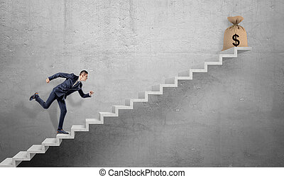 A businessman running up a concrete stairway with a tied hessian bag with a dollar sign on it.