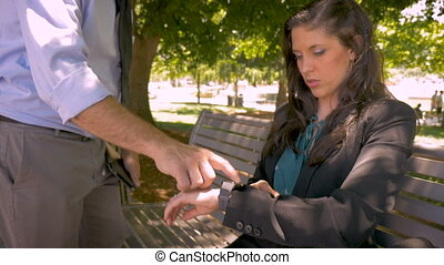 A businessman shows a businesswoman how to use her smart watch