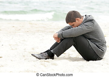A businessman sitting on the beach depressed