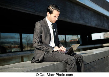 A businessman sitting on the floor with a laptop computer
