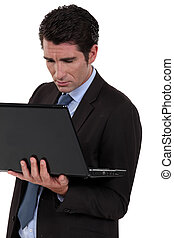 A businessman standing and typing on his laptop.