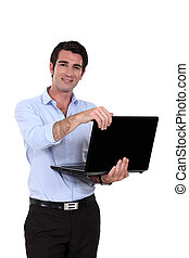A businessman standing with his laptop.