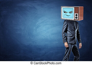 A businessman stands half-turned and ready to leave while wearing an old TV with a sceptic emoticon on his head.