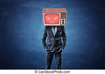 A businessman stands with hands in his pockets and wears a TV box on his head with a red screen showing an angry face.