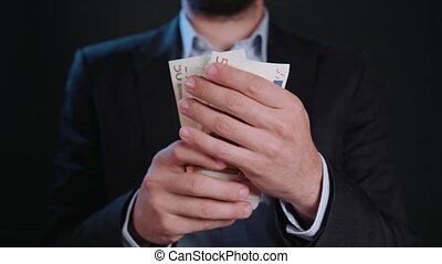 A Businessman Taking Cash out of His Wallet - A businessman...