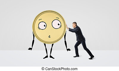 A businessman trying to push a golden coin with arms, legs and a face on white background.