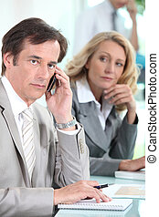 A businessman using a mobile phone and being observed by a businesswoman during a meeting.