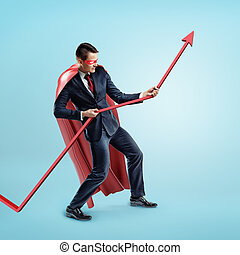 A businessman wearing a red superhero cape trying to hold a red statistic arrow with force on blue background.
