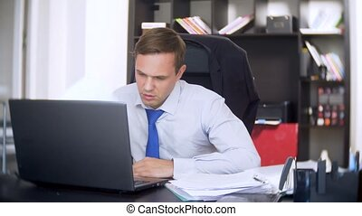 a businessman who scans documents, frowns, using a laptop,...