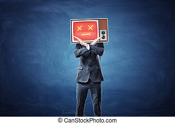 A businessman with a TV on his head showing a red face crosses his hands in prohibiting motion.