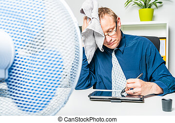 businessman works in the office on a hot day and sweats