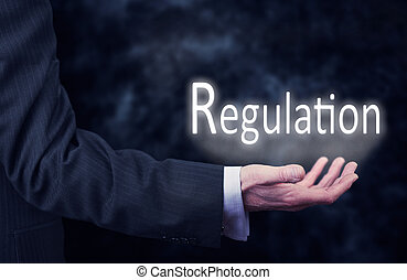 Regulation - A businessmans hand holding the word, ...