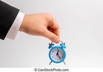 A businessman's hand holds a blue alarm clock on a white background. The concept of the flow of time, time to action. Hourly pay for work. Late for work and stay for part-time work. Time is money.