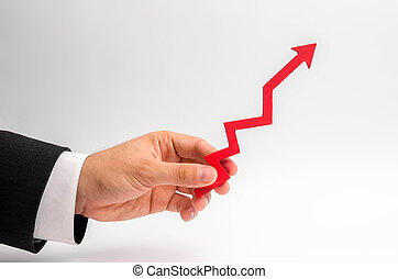 A businessman's hand holds a red arrow up on a white background. The concept of raising and multiplying income and profits, rising prices and salaries. High demand, positive economy.