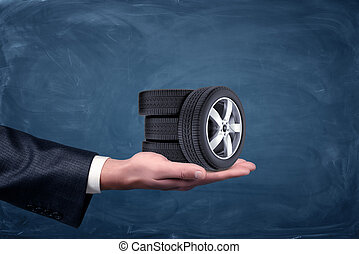 A businessman's hand on blue chalkboard background holding four tiny car wheels.