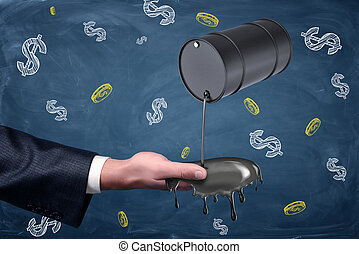 A businessman's hand reaching out to catch oil leaking from a small black barrel.